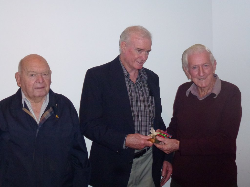 John Morrisey, youngest son of Bert Morrisey receives his father's medals from John Gilmour & Ron Badock.