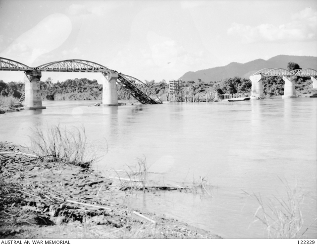 amarkan, Thailand. 21 October 1945. The eleven span steel bridge spanning the Mae Klong river (renamed Kwai Yai river in 1960). Dismantled by the Japanese in Java and transported to the site in 1942, the bridge was rebuilt using prisoner of war (POW) labour, and opened in April 1943. One span of the bridge was destroyed by Allied aircraft in mid February 1945. Note the wooden scaffolding and form work constructed by the Japanese in an attempt to repair the damaged spans. Tamarkan is fifty five kilometres north of Nong Pladuk (also known as Non Pladuk), or five kilometres north of Kanchanaburi (Kanburi as the POWs called it). (Donor B. Leemon)