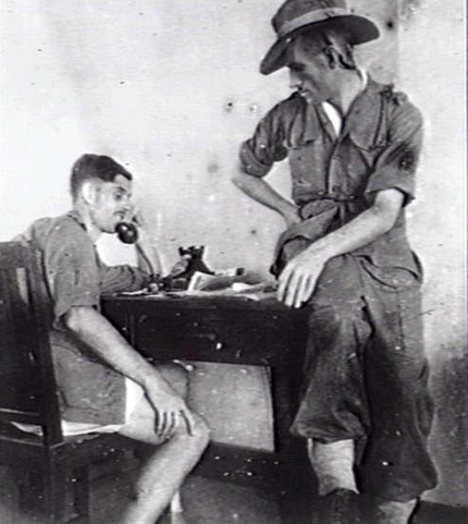 BANGKOK, THAILAND. 1945-09. FORMER PRISONERS OF WAR, HAVING BEEN ISSUED WITH NEW UNIFORMS, WAIT AT THE RECEPTION CAMP AT THE LAW UNIVERSITY FOR EVACUATION TO AUSTRALIA. LIEUTENANTS F. X. MCCAFFREY, 2/4TH MACHINE GUN BATTALION, SPEAKING ON THE TELEPHONE AND A.A. MITCHELL, 2/2ND PIONEER BATTALION. (DONOR C. MITCHELL)