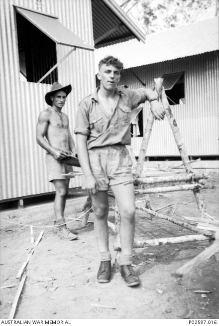 Darwin, NT. c. October 1941. WX8707 Private (Pte) Frank Nazzari and John Ramsbottom, both of 5 Platoon, A Company, 2/4th Machine Gun Battalion beside an A frame bed which they are constructing from bamboo and mangrove saplings to use at Winellie Camp. When the unit arrived at the camp, galvanised huts had been erected, but many were without concrete flooring and windows, requiring the first weeks at the camp to be spent finishing off the accommodation. Pte Nazzari later died of illness on 24 April 1945 in Borneo, whilst a Prisoner of War (POW). (Donor J. Lane)