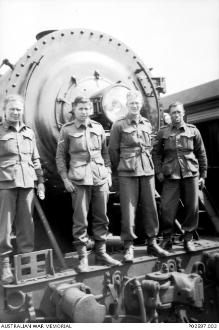 Quorn, SA. 11 October 1941. Group portrait of four members of A Company, 2/4th Machine Gun Battalion in front of a train locomotive en route from Woodside camp to Alice Springs. From left to right: Charlie Parke, WX7007 Edward George (Eddie) Burton (died of illness on 21 February 1945 in Sandakan, Borneo, whilst a Prisoner of War (POW)), A. S. Parke, unidentified.